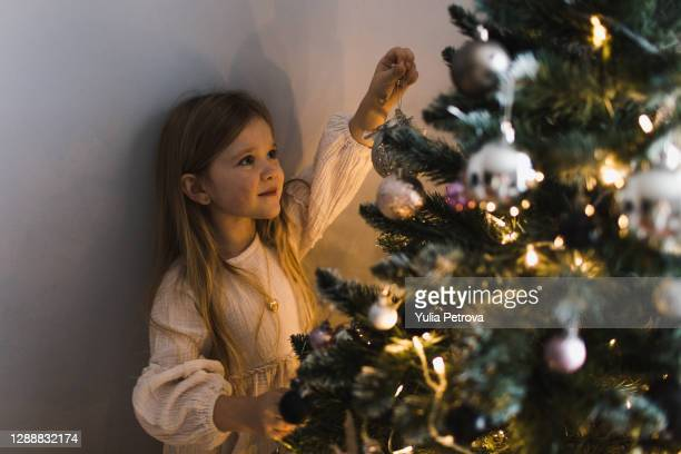 little girl in a dress decorates the christmas tree with toys and lights - scandinavian ethnicity stock pictures, royalty-free photos & images