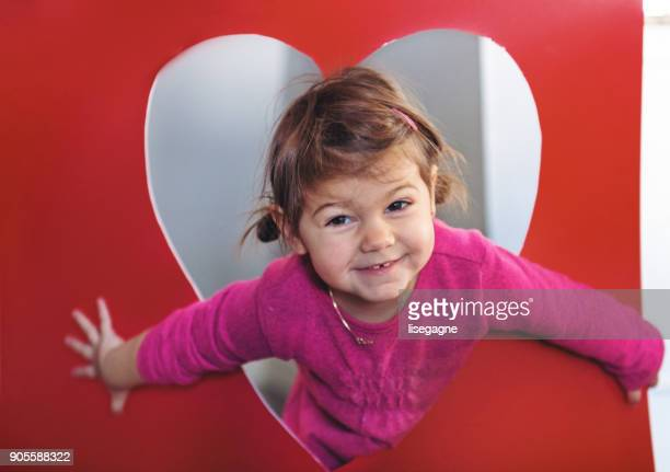 Little girl in a hear shape cardboard