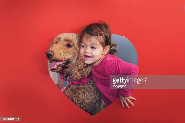 Little girl in a hear shape cardboard with her dog