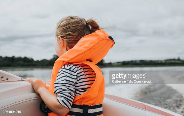 little girl in a lifejacket looking over the side pf a speedboat - sailing stock pictures, royalty-free photos & images