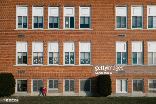 a little girl in a pink coat walks past a school building. - state school stock pictures, royalty-free photos & images