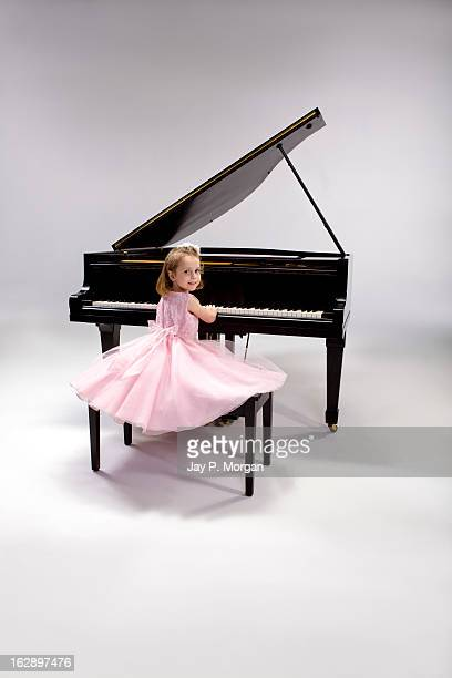 Little girl in a pink dress plays piano