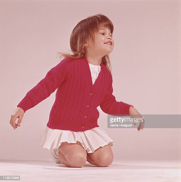 A little girl in a red cardigan and a white pleated skirt circa 1970