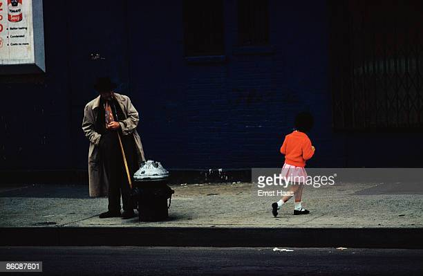 A little girl in a red cardigan passes a man on a street in New York City August 1962