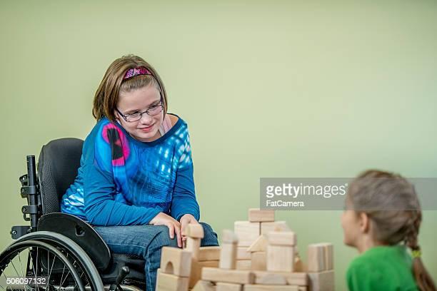 Niña en un jugando con su amigo para silla de ruedas