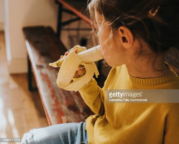 little girl in a yellow jumper eating a banana - vegetable stock pictures, royalty-free photos & images