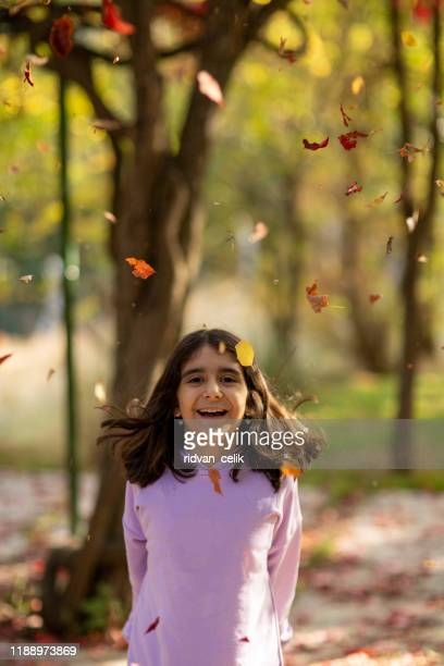 little girl in autumn park - beautiful turkish girl stock pictures, royalty-free photos & images