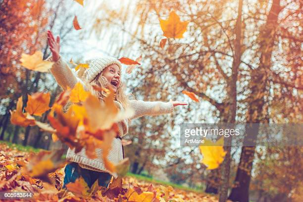 little girl in autumn park - herfst stockfoto's en -beelden