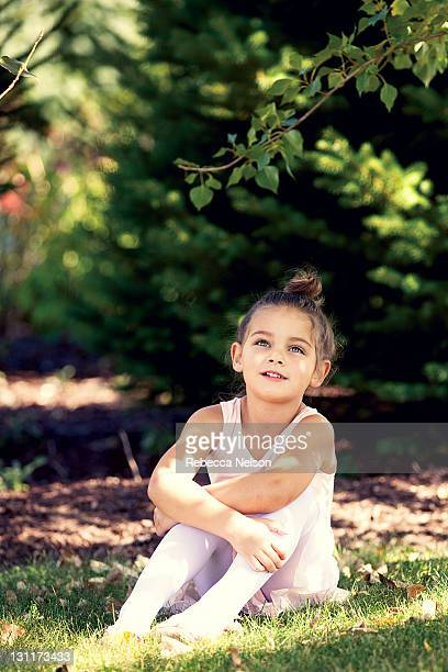 Little girl in ballerina outfit sitting on grass