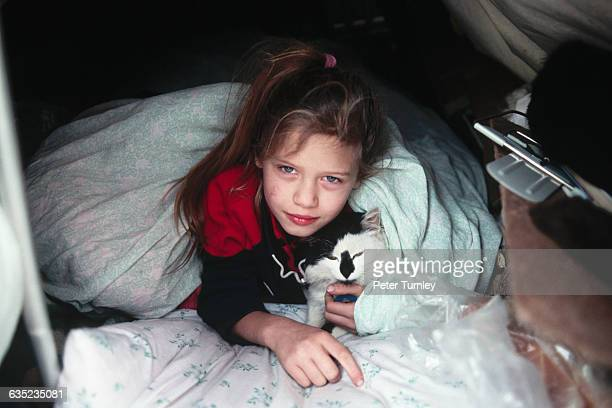 A little girl in bed with her cat They live in a shantytown behind the Kremlin in Moscow