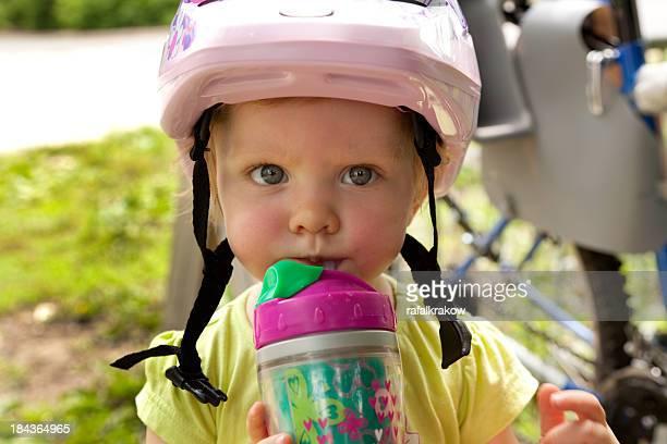 Little girl in bike helmet drinking water