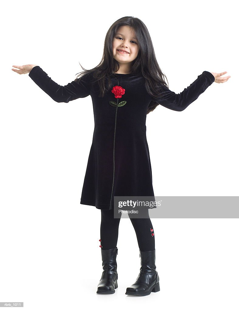 little girl in black dress holds out her arms and shrugs stock photo