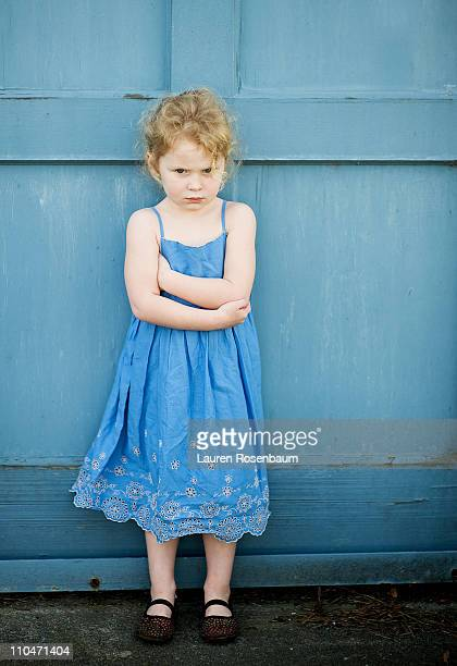 Little girl in blue dress against blue wall