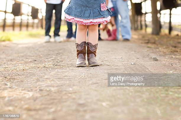 Little girl in boots on dirt road