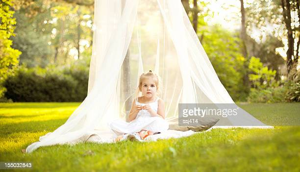 little girl in canopy under tree - mosquito net stock photos and pictures