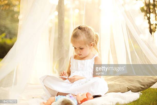 Little Girl in Canopy Under Tree with Doll