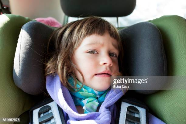 Little girl in car seat looks at camera in distrust.