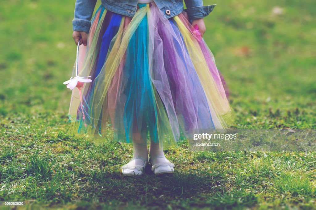 Little girl in colorful tutu skirt standing on green grass while holding magic wand : Stock Photo