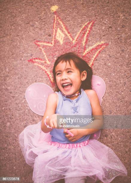 Little girl in fairy princess costume playing with chalk crown
