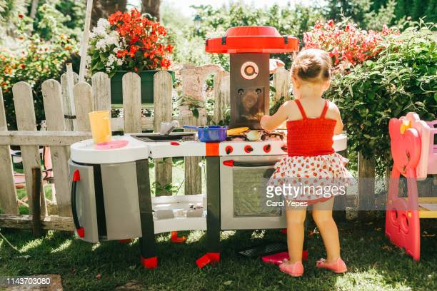 little girl in floral dress  playing with toy kitchen  in garden - carol cook stock pictures, royalty-free photos & images