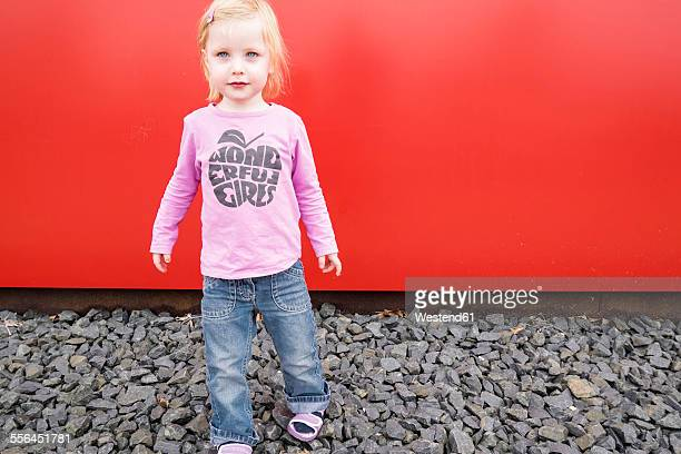 Little girl in front of a red wall