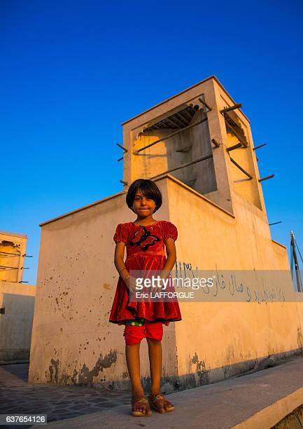 Little girl in front of a wind tower used as a natural cooling system on December 22 2015 in Laft Qeshm Island Iran