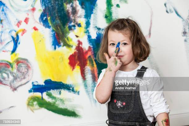 Little girl in front of painted white wall