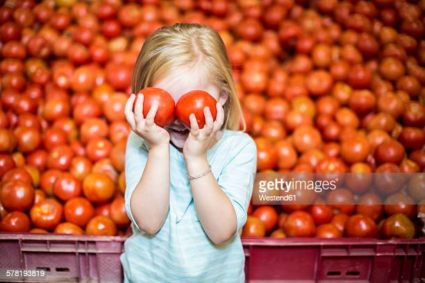 Little girl in front of tomato stall covering eyes with tomatoes