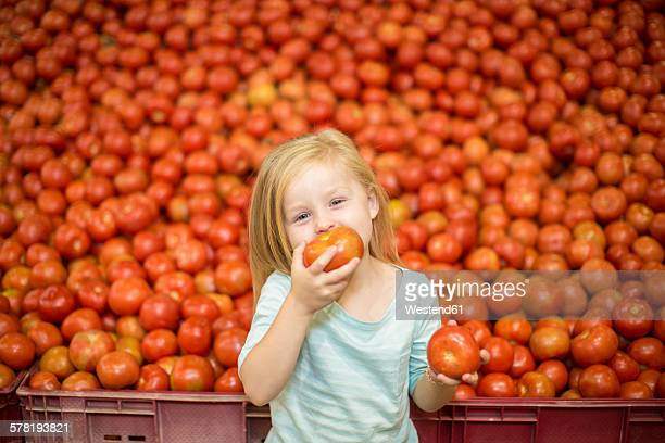 Little girl in front of tomato stall eating tomato