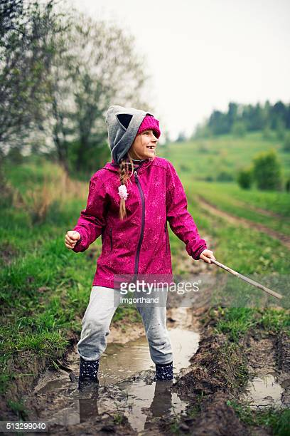Little girl in galoshes having spring fun with mud