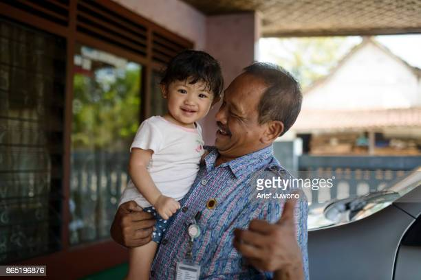 little girl in grandfather's arms