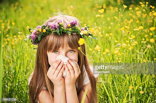 little girl in grass cleaning her nose - allergies stock photos and pictures