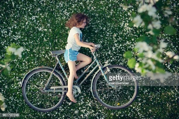 kleines Mädchen auf Wiese voller Apfelblüten