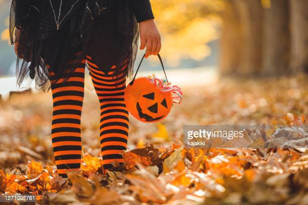 little girl in halloween costumes goes to trick or treating - trick or treat stock pictures, royalty-free photos & images