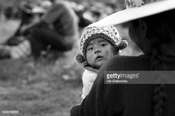 Little girl in her mother's arms in the Andes of Bolivia on April 15 2016 in Tawarchapi Bolivia