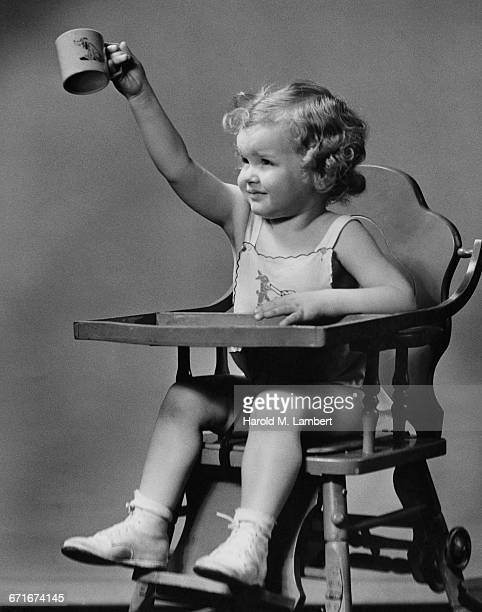 little girl in highchair and holding cup - {{relatedsearchurl(carousel.phrase)}} ストックフォトと画像