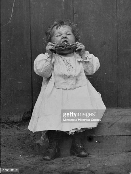 A little girl in Kenora Ontario sits and eats corn on the cob Canada ca 1910
