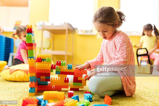Little girl in kindergarten playing with toy blocks.