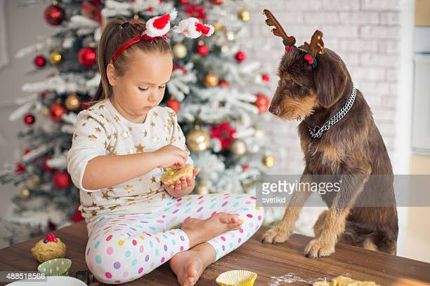Little girl in kitchen for christmas with her dog.
