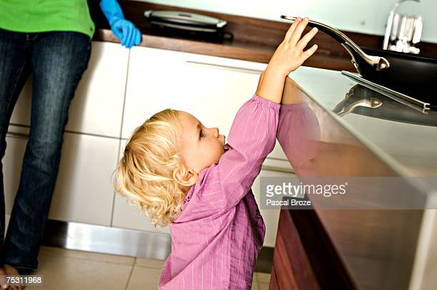 little girl in kitchen trying to catch a frying pan on stove, indoors - burn injury stock photos and pictures