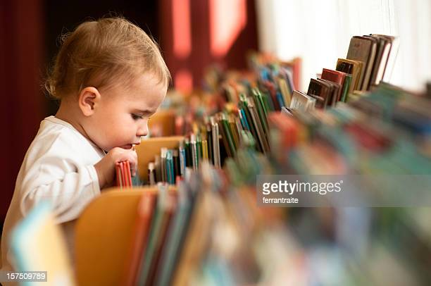 little girl in library - toddler stock pictures, royalty-free photos & images
