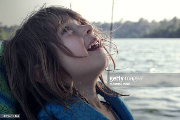 little girl in life jacket near water, looking up in awe - awe stock pictures, royalty-free photos & images