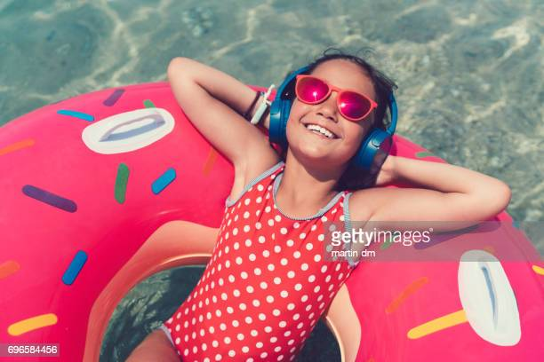 little girl in life preserver enjoying the music - little girl laying on the beach stock photos and pictures