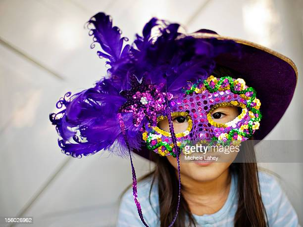 little girl in mardi gras mask and hat - mardi gras girls stock photos and pictures