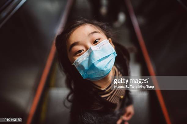 little girl in medical face mask looking up at camera joyfully on escalator - cubrebocas fotografías e imágenes de stock