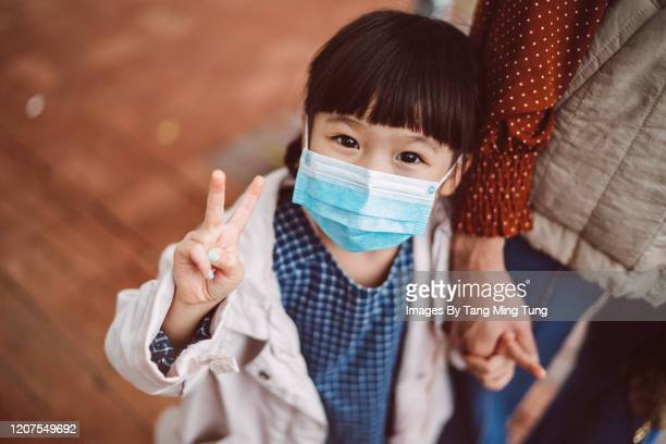 little girl in medical face mask making v-sign joyfully to the camera in street - innocence stock pictures, royalty-free photos & images
