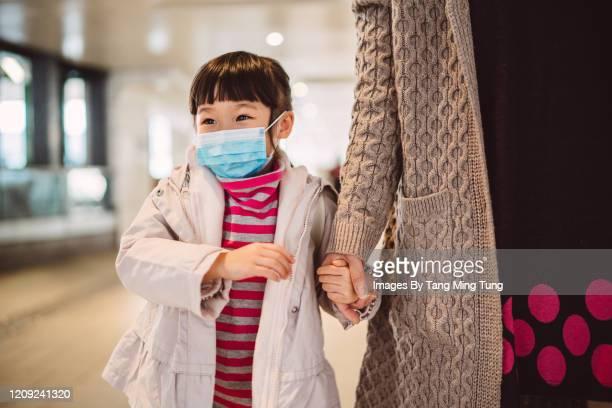 little girl in medical face mask strolling joyfully with mom in street - luchtvervuiling stockfoto's en -beelden