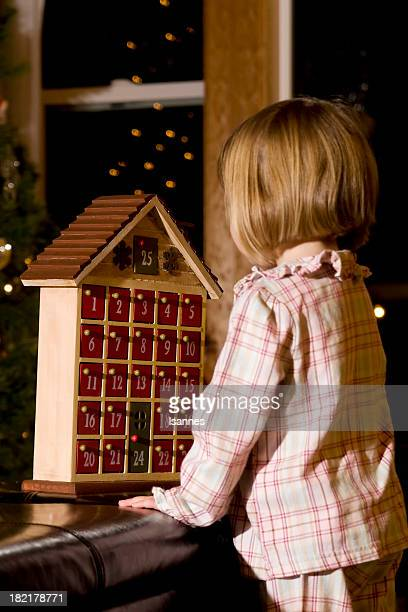a little girl in pajamas playing with an advent calendar - advent calendar stock photos and pictures