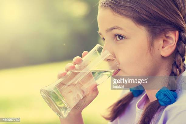 Little girl in pigtails drinking water from a glass