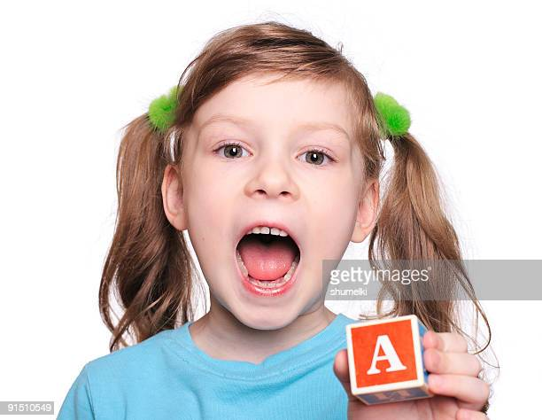 Little girl in pigtails holding letter block